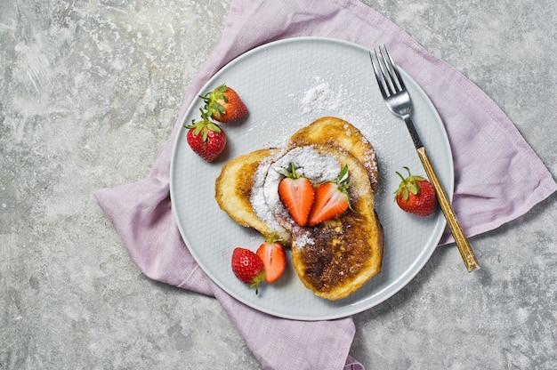 Französischer toast mit erdbeeren und ahornsirup auf einer grauen platte.
