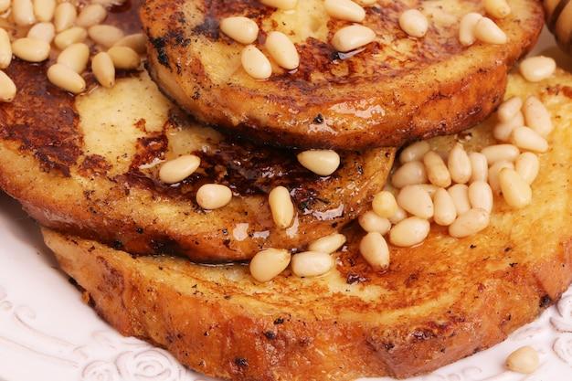 Französischer toast mit selektiver weichzeichnung der honigsirupcroutonkiefernnuss-frühstückssüßspeise
