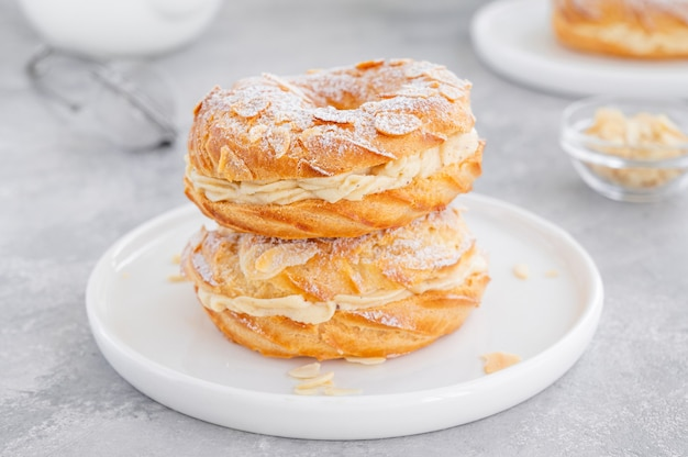 Französischer traditioneller kuchen paris brest mit pralinencreme, puderzucker und mandelblüten darüber
