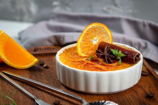 Französischer vanille creme brulee nachtisch in der keramischen schüssel auf hölzernem brett