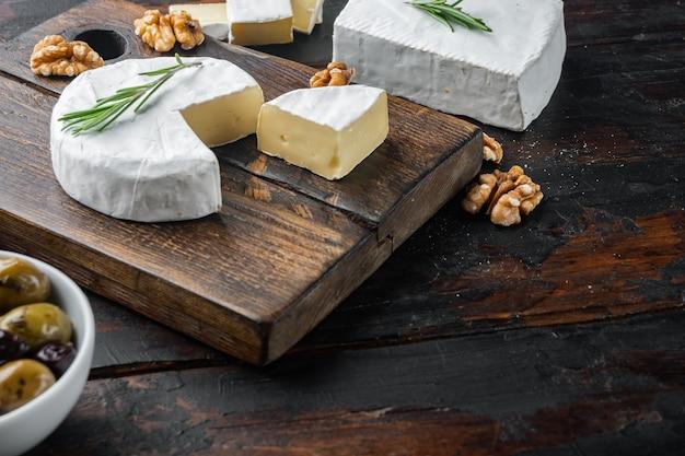 Französischer weicher camembert des normandie-käsesatzes, auf dunklem holztisch mit kopienraum