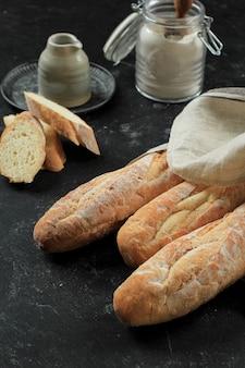 Französisches baguette-brot auf schwarzem marmortisch