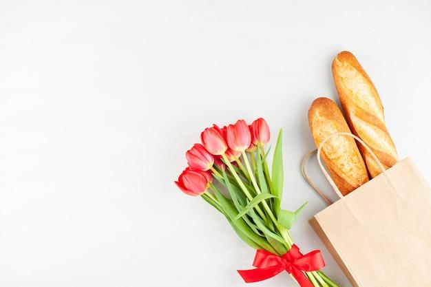 Französisches baguette in der einkaufstasche mit dem bouquet von roten tulpen