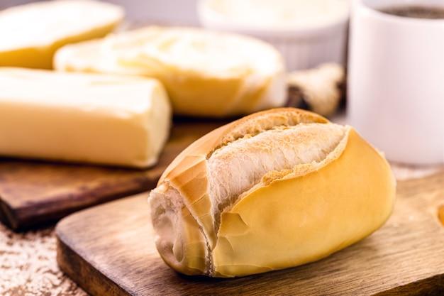 Französisches brot, brasilianisches brot, heiß serviert, mit butter und kaffee. nachmittags-snack