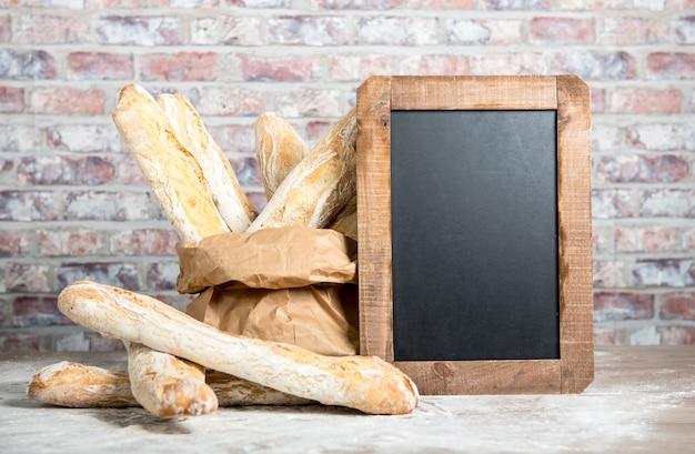 Französisches brot mit tafel auf einer rustikalen tabelle