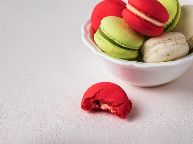 Französisches coockie macaron oder makronen auf hellem hintergrund mit frühlingsblumen, pastellfarben.