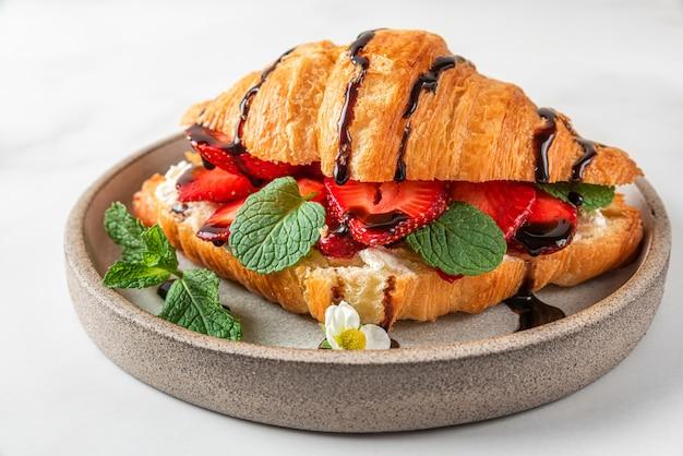 Französisches croissant-sandwich mit frischen erdbeeren, frischkäse, minze und schokoladensauce auf weißem hintergrund