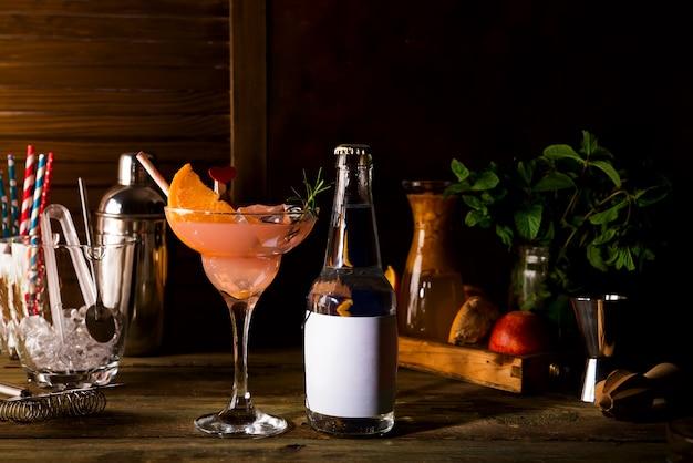 Französisches daiquiricocktail mit frischer orange und einer flasche tonikum und kopienraum