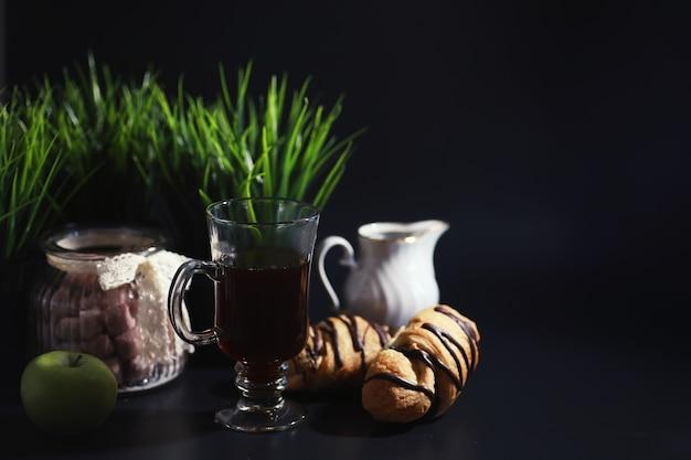 Französisches frühstück auf dem tisch. kaffee-croissant mit schokolade und eine karaffe mit sahne. frisches gebäck und entkoffeinierter kaffee.