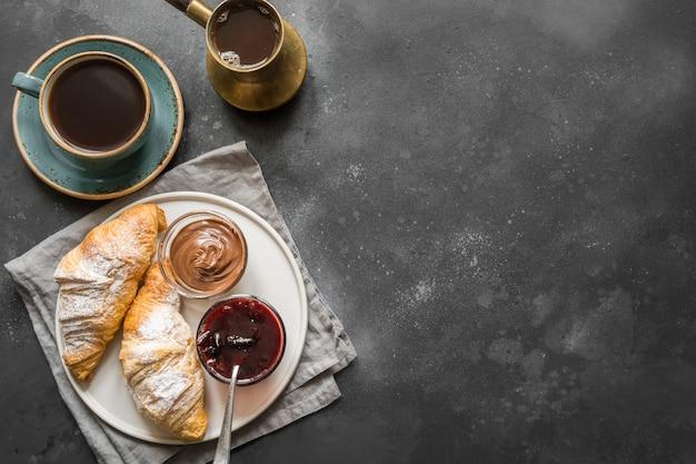 Französisches frühstück des konzeptes mit schwarzem kaffee und hörnchen. ansicht von oben. kopieren sie platz für text.