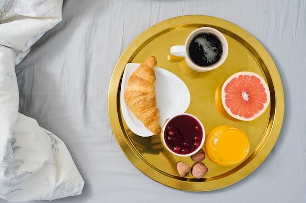 Französisches frühstück im hotel. kaffee, marmelade, croissant, orangensaft, grapefruit, litschi.