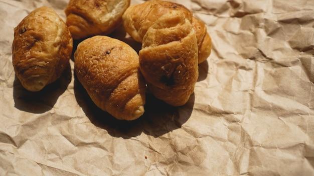 Französisches frühstück mit croissant, kraftgeschirr auf kraftpapier. mini-croissants