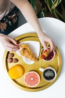 Französisches frühstück mit croissant und kaffee. frauenhände brechen croissant. kaffee, marmelade, croissant, orangensaft, grapefruit, litschi.