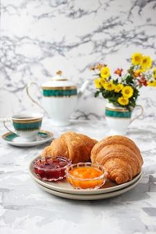 Französisches frühstück mit hörnchen, aprikosenmarmelade, kirschmarmelade und einer tasse tee, roten und gelben blumen