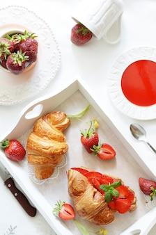 Französisches frühstück mit hörnchen- und erdbeermarmelade
