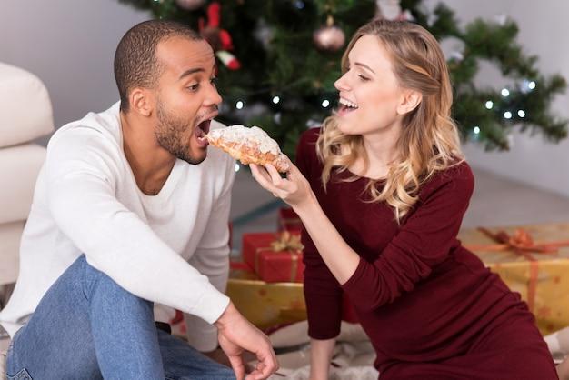 Französisches gebäck. schöne glückliche blonde frau, die ein croissant hält und es ihrem freund anbietet, während sie spaß mit ihm hat