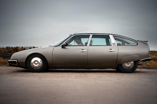 Französisches klassisches auto und frau gekleidet im weinlesestil, am regnerischen tag, entspannen sie stimmung