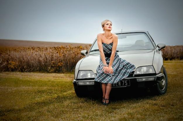 Französisches klassisches auto und schöne blonde frau im französischen stil gekleidet, die nahe lavendelfeld gehen