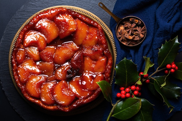 Französisches lebensmittelkonzept hausgemacht auf dem kopf stehender apfelkaramellkuchen tarte tatin aux pomme auf schwarzem schiefersteinbrett mit kopierraum