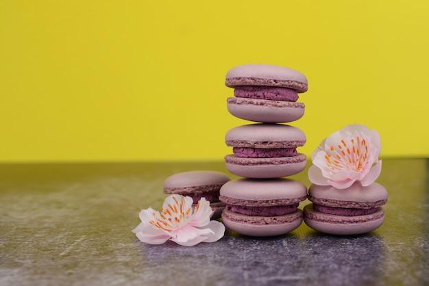 Französisches macaron keksenachtisch-rosaflieder auf einem gelben hintergrund mit rosa blumen