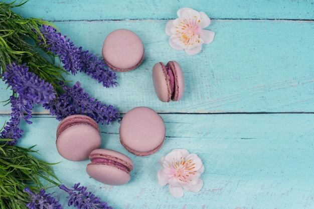 Französisches macaron keksenachtisch-rosaflieder auf einem hintergrund des dunklen schwarzen