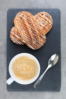 Französisches zimtbrötchen auf schwarzem schieferbrett mit weißer tasse kaffee klassische französische bäckereien flach