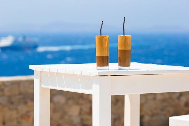 Frappe, eiskaffee am strand. sommer gefrorener kaffee frappuccino, frappe oder latte in einem hohen glashintergrund das meer in der strandbar