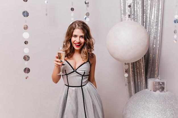 Frau 25 jahre in schönen hellen kleid mit glas champagner in den händen, spaß am vorabend der weihnachtsferien