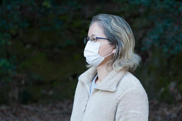Frau 40-49 jahre im freien, trägt eine brille und eine weiße maske zum schutz vor coronavirus