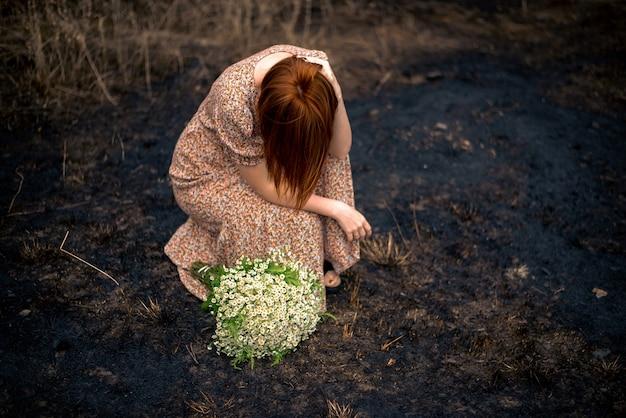 Frau 40 jahre alt mit einem strauß wildblumen auf der verbrannten erde, psychologisches burnout-konzept