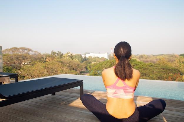 Frau 40s, die yoga nahe swimmingpool auf der dachspitze tut. gesundes lebensstilkonzept