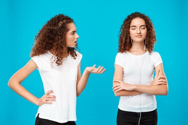 Frau ärgert sich über ihren schwesterzwilling in kopfhörern über blau.