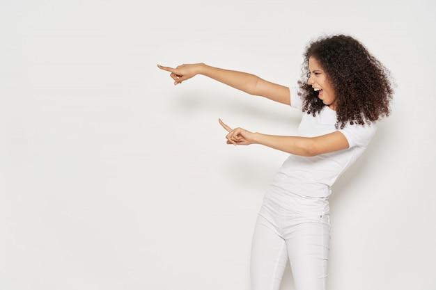 Frau afroamerikaner in einem t-shirt, das auf copyspace zeigt