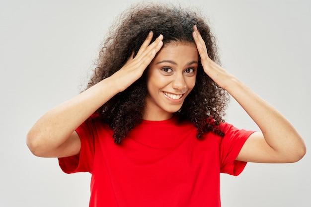 Frau afroamerikaner in einem t-shirt im studio auf einem farbigen hintergrund, der aufwirft
