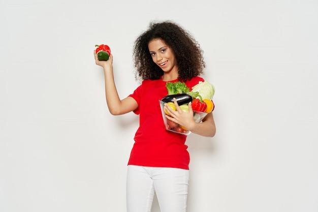 Frau afroamerikaner in einem t-shirt im studio auf einer farbigen oberfläche posiert