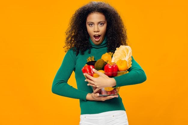 Frau afroamerikaner in einem t-shirt raum auf einem farbigen raum posiert