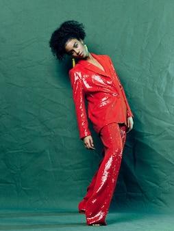 Frau afroamerikaner in glänzenden festlichen modekleidung auf einem farbigen hintergrund, der aufwirft