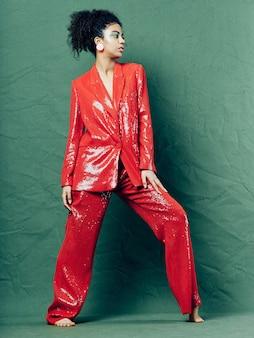 Frau afroamerikaner in glänzenden festlichen modekleidung auf einer farbigen oberfläche, die aufwirft