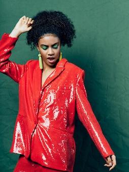 Frau afroamerikaner in glänzenden festlichen modekleidung auf einer farbigen raumaufstellung