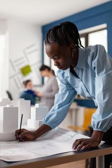 Frau afroamerikanischer abstammung, die als architektin in einem professionellen büro arbeitet. ingenieurkonstrukteur am schreibtisch, der auf blaupausenplan für den bau von modellmaquette schaut. entwicklungsprojekt
