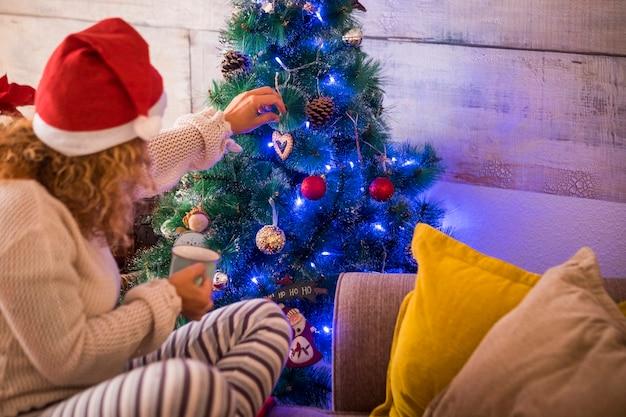Frau allein zu hause am weihnachtstag, die den weihnachtsbaum mit einer tasse tee oder kaffee in der hand berührt und macht