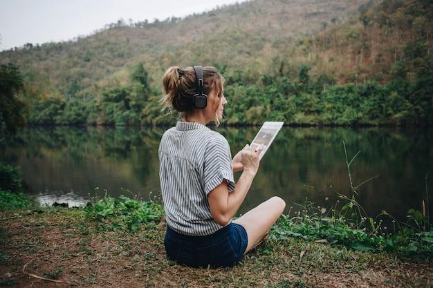 Frau alleine in der natur, die musik mit kopfhörern hört