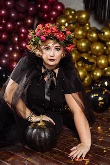 Frau als hexe mit blumen auf dem kopf verkleidet