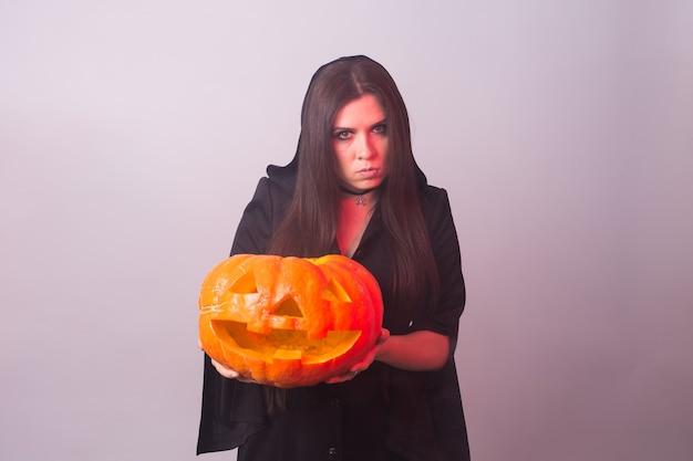 Frau als hexe steht mit dem kürbis auf weißer wand mit kopienraum. halloween- und karnevalskonzept