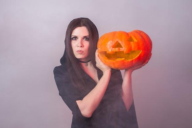 Frau als hexe steht mit dem kürbis halloween- und karnevalskonzept.
