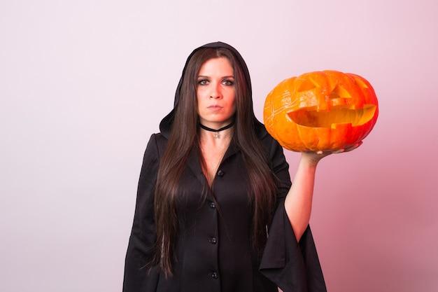 Frau als hexe steht mit dem kürbis im studio