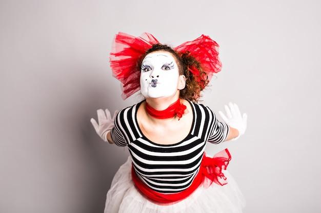 Frau als pantomime, die einen kuss schickt. konzept der liebe und des aprilscherztages