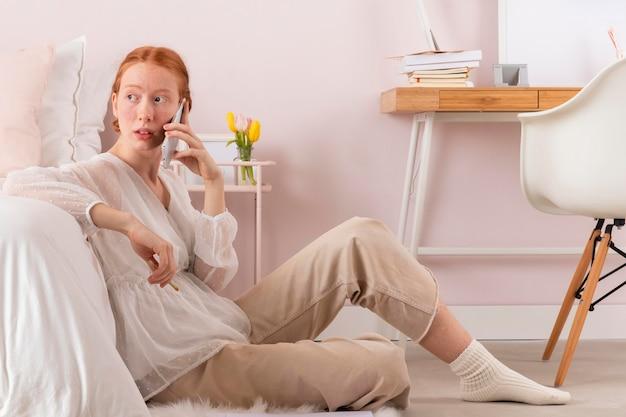 Frau am arbeitsplatz mit handy