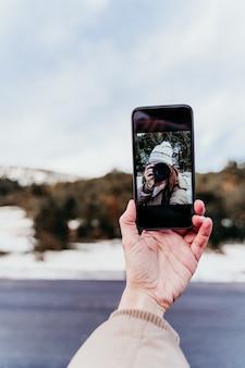 Frau am berg, die ein selbstporträt auf handy mit kamera nimmt. wintersaison