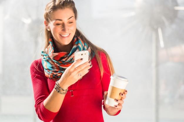 Frau am brunnen mit telefon und kaffee